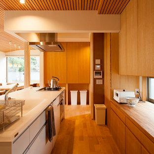 他の地域の中サイズのカントリー風おしゃれなキッチン (一体型シンク、インセット扉のキャビネット、中間色木目調キャビネット、人工大理石カウンター、白いキッチンパネル、白い調理設備、無垢フローリング、ベージュの床、白いキッチンカウンター) の写真