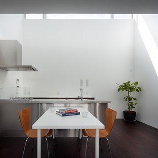 他の地域のモダンスタイルのおしゃれなキッチン (ステンレスカウンター、フラットパネル扉のキャビネット、ステンレスキャビネット、白いキッチンパネル、濃色無垢フローリング、茶色い床、グレーのキッチンカウンター) の写真