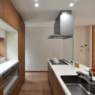 Design ideas for a medium sized modern single-wall open plan kitchen in Other with an integrated sink, flat-panel cabinets, light wood cabinets, composite countertops, plywood flooring and an island.