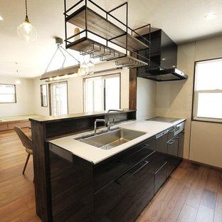 他の地域のアジアンスタイルのおしゃれなキッチン (アンダーカウンターシンク、フラットパネル扉のキャビネット、黒いキャビネット、人工大理石カウンター、白いキッチンパネル、ガラス板のキッチンパネル、シルバーの調理設備、合板フローリング、茶色い床、白いキッチンカウンター) の写真