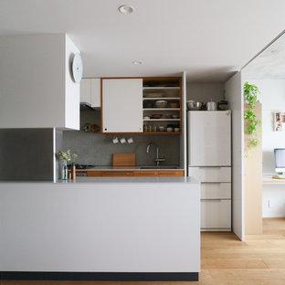 東京23区のモダンスタイルのおしゃれなキッチン (アンダーカウンターシンク、フラットパネル扉のキャビネット、中間色木目調キャビネット、グレーのキッチンパネル、白い調理設備、淡色無垢フローリング、白いキッチンカウンター) の写真