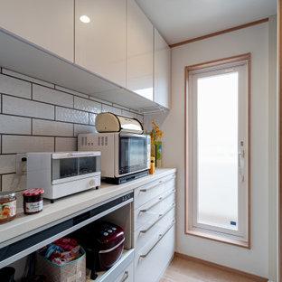 Cette photo montre une cuisine ouverte linéaire avec un évier 1 bac, un placard à porte plane, des portes de placard blanches, une crédence blanche, un sol en contreplaqué, un sol marron, un plan de travail beige et un plafond en papier peint.