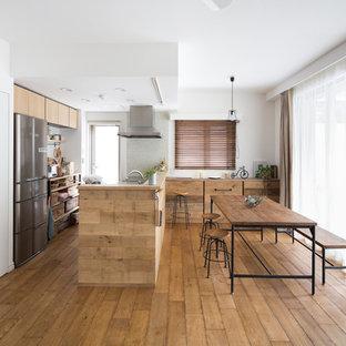 他の地域のアジアンスタイルのおしゃれなキッチン (フラットパネル扉のキャビネット、淡色木目調キャビネット、シルバーの調理設備の、無垢フローリング、茶色い床) の写真