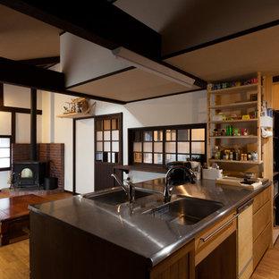 他の地域の大きい和風のおしゃれなキッチン (ダブルシンク、フラットパネル扉のキャビネット、茶色いキャビネット、ステンレスカウンター、無垢フローリング、茶色い床) の写真