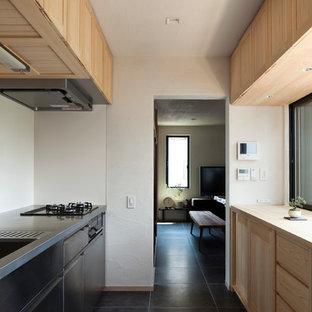東京23区の中くらいの和風のおしゃれなキッチン (一体型シンク、落し込みパネル扉のキャビネット、淡色木目調キャビネット、ステンレスカウンター、グレーの床) の写真