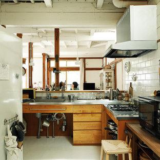 東京都下のアジアンスタイルのおしゃれなキッチン (シングルシンク、フラットパネル扉のキャビネット、中間色木目調キャビネット、ステンレスカウンター、白いキッチンパネル、白い床) の写真