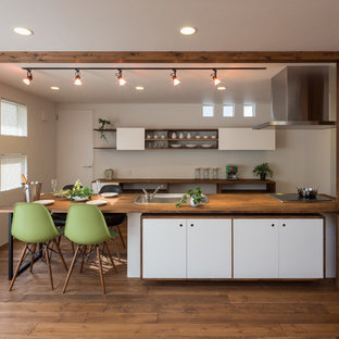 Inspiration for an asian galley eat-in kitchen in Other with a drop-in sink, flat-panel cabinets, white cabinets, wood benchtops, white splashback, stainless steel appliances, medium hardwood floors, with island and brown floor.