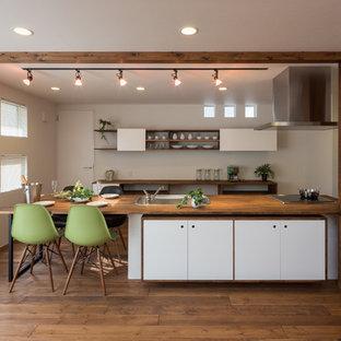 他の地域のアジアンスタイルのおしゃれなキッチン (ドロップインシンク、フラットパネル扉のキャビネット、白いキャビネット、木材カウンター、白いキッチンパネル、シルバーの調理設備の、無垢フローリング、茶色い床) の写真