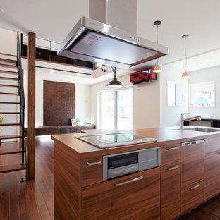 アジアンスタイルのおしゃれなキッチン (アンダーカウンターシンク、フラットパネル扉のキャビネット、中間色木目調キャビネット、茶色いキッチンパネル、シルバーの調理設備の、濃色無垢フローリング、茶色い床) の写真
