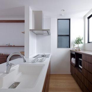 他の地域のアジアンスタイルのおしゃれなII型キッチン (アンダーカウンターシンク、フラットパネル扉のキャビネット、中間色木目調キャビネット、無垢フローリング、アイランドなし、ベージュの床、白いキッチンカウンター) の写真
