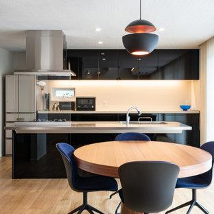 福岡のコンテンポラリースタイルのおしゃれなキッチン (一体型シンク、フラットパネル扉のキャビネット、黒いキャビネット、シルバーの調理設備、ベージュの床、グレーのキッチンカウンター) の写真