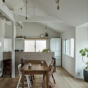他の地域の小さいシャビーシック調のおしゃれなキッチン (一体型シンク、インセット扉のキャビネット、白いキャビネット、ステンレスカウンター、白いキッチンパネル、セラミックタイルのキッチンパネル、黒い調理設備、淡色無垢フローリング、白い床、グレーのキッチンカウンター) の写真