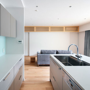 Design ideas for a small contemporary galley open plan kitchen in Osaka with a built-in sink, beaded cabinets, grey cabinets, laminate countertops, white splashback, glass tiled splashback, plywood flooring, an island, beige floors and white worktops.