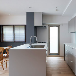 Photo of a small contemporary galley open plan kitchen in Osaka with a built-in sink, beaded cabinets, grey cabinets, laminate countertops, white splashback, glass tiled splashback, plywood flooring, an island, beige floors and white worktops.