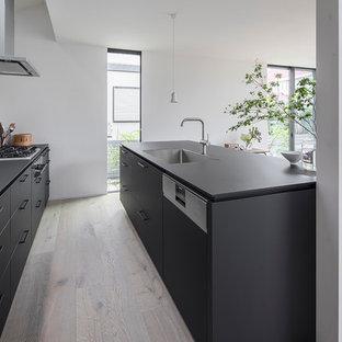 Foto di una cucina stile rurale con lavello sottopiano, ante a filo, ante nere, elettrodomestici in acciaio inossidabile, parquet chiaro, isola, pavimento beige e top nero