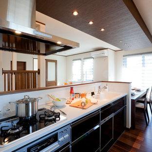 他の地域のアジアンスタイルのおしゃれなキッチン (一体型シンク、フラットパネル扉のキャビネット、黒いキャビネット、白いキッチンパネル、濃色無垢フローリング、茶色い床) の写真