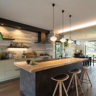 Asian open concept kitchen designs - Open concept kitchen - single-wall brown floor open concept kitchen idea in Tokyo with an undermount sink, beaded inset cabinets, distressed cabinets, black appliances, an island and black countertops