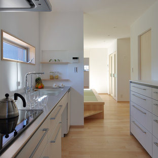 大阪のモダンスタイルのおしゃれなキッチン (白いキャビネット、ステンレスカウンター、白いキッチンパネル、淡色無垢フローリング、アイランドなし) の写真