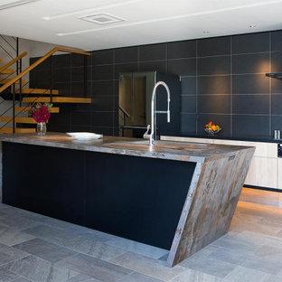 コンテンポラリースタイルのおしゃれなキッチン (アンダーカウンターシンク、淡色木目調キャビネット、黒いキッチンパネル、黒い調理設備、グレーの床、マルチカラーのキッチンカウンター) の写真
