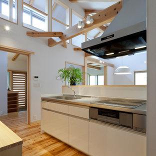 他の地域の中サイズの和風のおしゃれなキッチン (一体型シンク、フラットパネル扉のキャビネット、白いキャビネット、ステンレスカウンター、白いキッチンパネル、ガラス板のキッチンパネル、白い調理設備、淡色無垢フローリング、ベージュの床、ベージュのキッチンカウンター) の写真