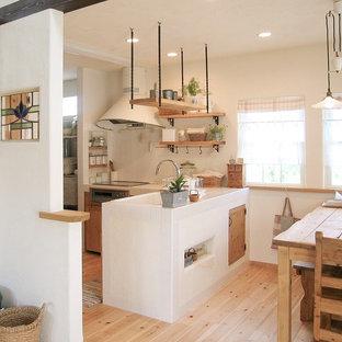 他の地域の中サイズのカントリー風おしゃれなキッチン (アンダーカウンターシンク、インセット扉のキャビネット、中間色木目調キャビネット、タイルカウンター、白いキッチンパネル、ガラスタイルのキッチンパネル、パネルと同色の調理設備、無垢フローリング、アイランドなし、ベージュの床、白いキッチンカウンター) の写真