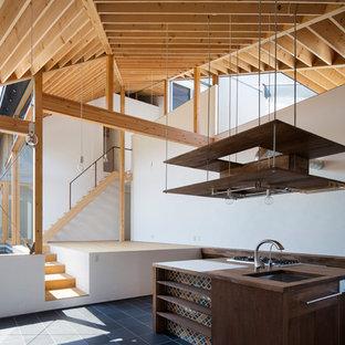 大阪のアジアンスタイルのおしゃれなキッチン (アンダーカウンターシンク、フラットパネル扉のキャビネット、濃色木目調キャビネット、木材カウンター、白いキッチンパネル、青い床、茶色いキッチンカウンター) の写真
