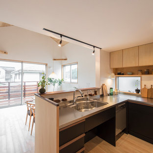 Scandinavian l-shaped kitchen in Yokohama with an integrated sink, black cabinets, stainless steel benchtops, porcelain splashback and stainless steel appliances.