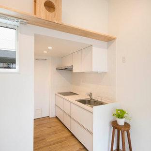 東京23区の小さい北欧スタイルのおしゃれなキッチン (アンダーカウンターシンク、インセット扉のキャビネット、白いキャビネット、人工大理石カウンター、白いキッチンパネル、モザイクタイルのキッチンパネル、白い調理設備、淡色無垢フローリング、ベージュの床、白いキッチンカウンター、クロスの天井) の写真