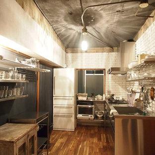 他の地域の小さいインダストリアルスタイルのおしゃれなキッチン (シングルシンク、フラットパネル扉のキャビネット、ステンレスキャビネット、ステンレスカウンター、白いキッチンパネル、レンガのキッチンパネル、無垢フローリング、茶色い床) の写真