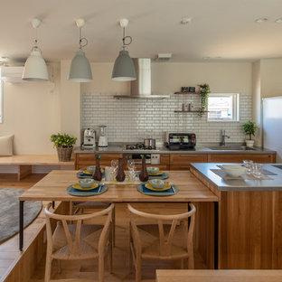 東京都下のアジアンスタイルのおしゃれなキッチン (シングルシンク、シェーカースタイル扉のキャビネット、中間色木目調キャビネット、ステンレスカウンター、白いキッチンパネル、サブウェイタイルのキッチンパネル、白い調理設備、無垢フローリング、ベージュの床、グレーのキッチンカウンター) の写真