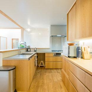 他の地域の北欧スタイルのおしゃれなキッチン (シングルシンク、フラットパネル扉のキャビネット、中間色木目調キャビネット、ステンレスカウンター、無垢フローリング、茶色い床) の写真