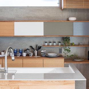 他の地域のコンテンポラリースタイルのおしゃれなキッチン (フラットパネル扉のキャビネット、中間色木目調キャビネット、グレーのキッチンパネル、石スラブのキッチンパネル) の写真