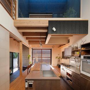 東京23区のアジアンスタイルのおしゃれなキッチン (淡色無垢フローリング、シングルシンク、フラットパネル扉のキャビネット、ステンレスキャビネット、ステンレスカウンター、白いキッチンパネル、茶色い床) の写真