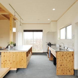 他の地域のII型アジアンスタイルのLDKの画像 (ステンレスカウンター、フラットパネル扉のキャビネット、中間色木目調キャビネット、白いキッチンパネル、コンクリートの床、アイランド1つ、グレーの床)