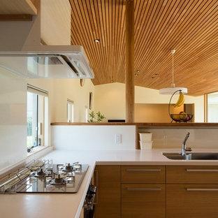 Lantlig inredning av ett stort vit vitt kök, med en undermonterad diskho, luckor med profilerade fronter, skåp i mellenmörkt trä, bänkskiva i koppar, vitt stänkskydd, glaspanel som stänkskydd, rostfria vitvaror, heltäckningsmatta, en köksö och beiget golv