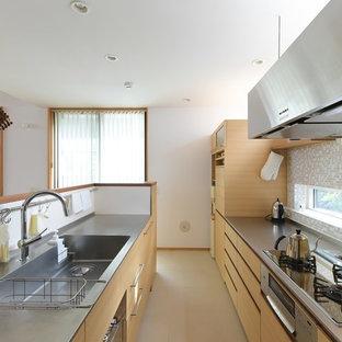 他の地域のコンテンポラリースタイルのおしゃれなII型キッチン (一体型シンク、フラットパネル扉のキャビネット、淡色木目調キャビネット、ステンレスカウンター、マルチカラーのキッチンパネル、モザイクタイルのキッチンパネル、ベージュの床) の写真
