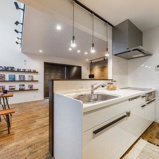 東京都下のインダストリアルスタイルのおしゃれなキッチン (シングルシンク、フラットパネル扉のキャビネット、白いキャビネット、白いキッチンパネル、無垢フローリング、茶色い床) の写真