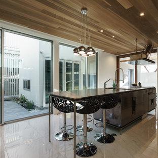 東京23区のコンテンポラリースタイルのおしゃれなキッチン (フラットパネル扉のキャビネット、黒いキャビネット、大理石の床、ベージュの床) の写真