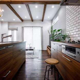 東京23区のミッドセンチュリースタイルのおしゃれなキッチン (アンダーカウンターシンク、インセット扉のキャビネット、中間色木目調キャビネット、白いキッチンパネル、サブウェイタイルのキッチンパネル、シルバーの調理設備、濃色無垢フローリング、茶色い床、茶色いキッチンカウンター) の写真