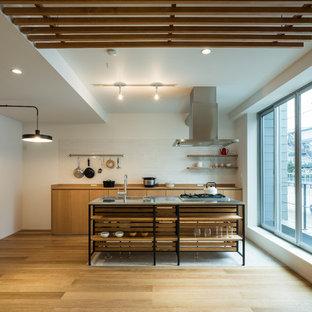 東京23区のアジアンスタイルのおしゃれなキッチン (フラットパネル扉のキャビネット、中間色木目調キャビネット、白いキッチンパネル、サブウェイタイルのキッチンパネル、無垢フローリング、茶色い床、茶色いキッチンカウンター) の写真