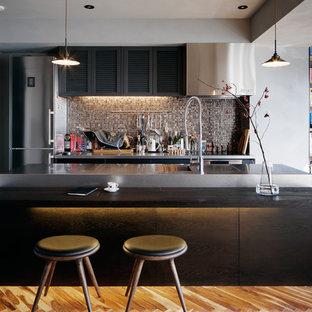 東京23区のエクレクティックスタイルのおしゃれなキッチン (一体型シンク、フラットパネル扉のキャビネット、無垢フローリング、茶色い床、黒いキッチンカウンター) の写真