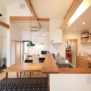 他の地域の北欧スタイルのおしゃれなキッチン (シングルシンク、落し込みパネル扉のキャビネット、淡色木目調キャビネット、ステンレスカウンター、淡色無垢フローリング、茶色い床、茶色いキッチンカウンター) の写真