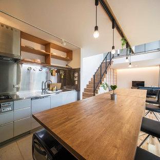 東京23区のアジアンスタイルのおしゃれなキッチン (シングルシンク、フラットパネル扉のキャビネット、グレーのキャビネット、ステンレスカウンター、メタリックのキッチンパネル、茶色い床) の写真