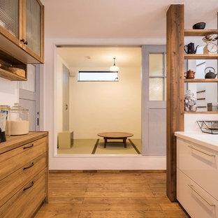 東京都下のアジアンスタイルのおしゃれなアイランドキッチン (フラットパネル扉のキャビネット、中間色木目調キャビネット、無垢フローリング、茶色い床) の写真