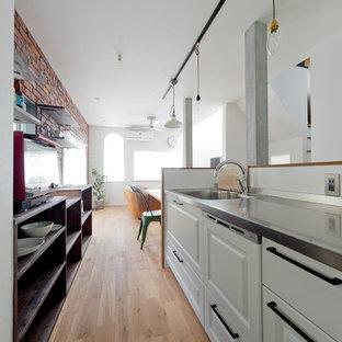 大阪のおしゃれなキッチン (シングルシンク、インセット扉のキャビネット、白いキャビネット、ステンレスカウンター、淡色無垢フローリング、茶色い床) の写真