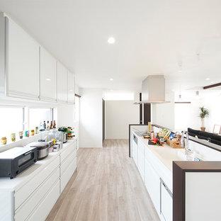 他の地域のモダンスタイルのおしゃれなキッチン (一体型シンク、フラットパネル扉のキャビネット、白いキャビネット、グレーの床、白いキッチンカウンター) の写真