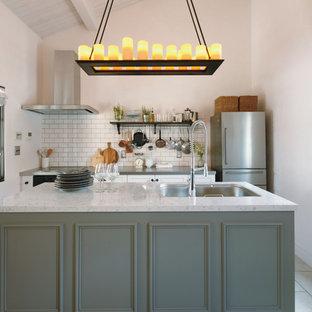 他の地域のトランジショナルスタイルのおしゃれなキッチン (アンダーカウンターシンク、グレーのキャビネット、大理石カウンター、白いキッチンパネル、ガラスタイルのキッチンパネル、ベージュの床) の写真