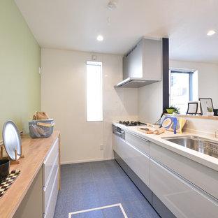 他の地域のコンテンポラリースタイルのおしゃれなI型キッチン (白いキャビネット、白いキッチンパネル、白い調理設備、青い床、茶色いキッチンカウンター) の写真