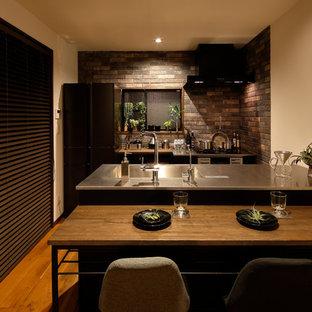 他の地域のアジアンスタイルのおしゃれなペニンシュラキッチン (シングルシンク、黒いキャビネット、ステンレスカウンター、茶色いキッチンパネル、無垢フローリング、茶色い床、黒いキッチンカウンター) の写真