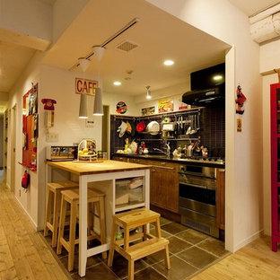 東京23区のエクレクティックスタイルのおしゃれなキッチン (シングルシンク、フラットパネル扉のキャビネット、中間色木目調キャビネット、ステンレスカウンター、青いキッチンパネル、茶色い床、茶色いキッチンカウンター) の写真